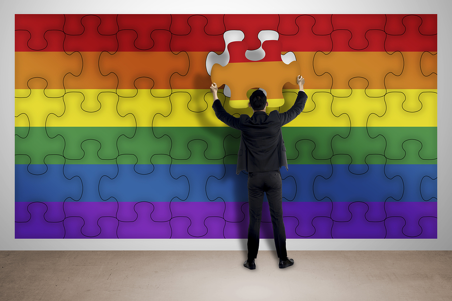 man putting together final jigsaw pieces to complete a Pride flag